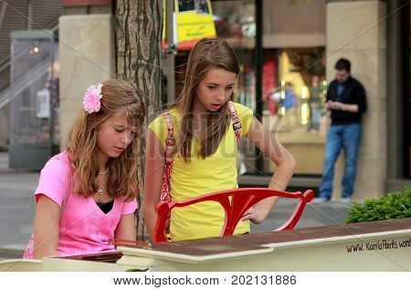 Denver, Colorado - May 5, 2011: Two girls playing piano on 16th street in downtown Denver during the street festival.