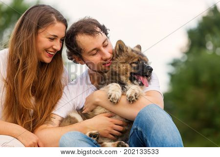 Portrait Of A Young Couple With An Elo Puppy