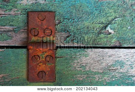 A close up image of an old rusted door hinge on weathered wood.