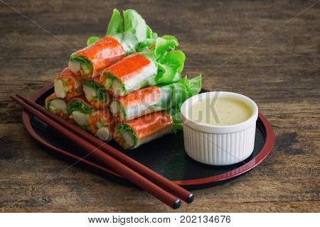 Fresh spring rolls with fresh vegetable and crab stick served with wasabi mixed salad cream dipping sauce. Rolls salad or fresh spring roll in Japanese style healthy tasty food for appetizer or meal. Fresh spring rolls in fusion food style.
