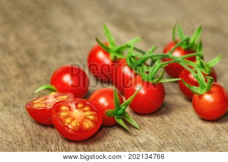 Fresh cherry tomato on rustic wood table. Close up lovely cherry tomato for background or wallpaper. Prepare fresh cut cherry tomato for home cooking look so delicious. Macro concept with copy space. Cherry tomato for vegetable concept.