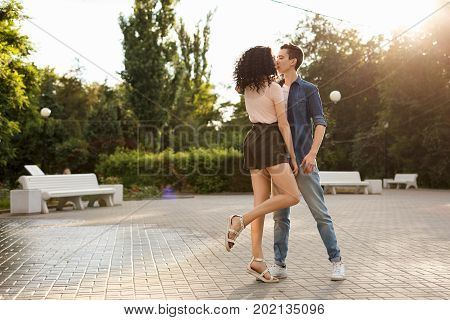 Teenagers are dancing in the city park. Couple in love. Romantic first date. Carefree youth