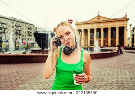 Girl in red jacket listening to music streaming with headphones with a cuo of coffee in hand.