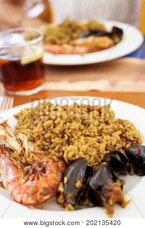 closeup of some plates with a typical spanish seafood paella on a table set for lunch, next to a glass with sangria