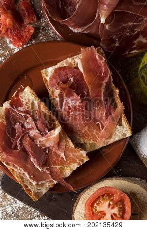 high-angle shot of an earthenware plate with typical catalan pa amb tomaquet, bread with tomato dressed with olive oil, topped with serrano ham, on a rustic wooden table