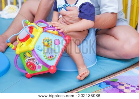 Father Training His Son to Use the Potty Cute little Asian 1 year old toddler baby boy child sitting on potty and holding colorful toy.Training child concept.