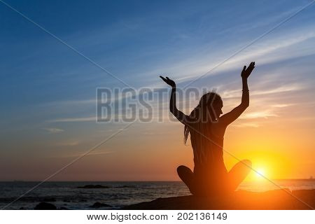 Young woman in a meditating yoga pose overlooking the amazing sunset. Mind body spirit concept.