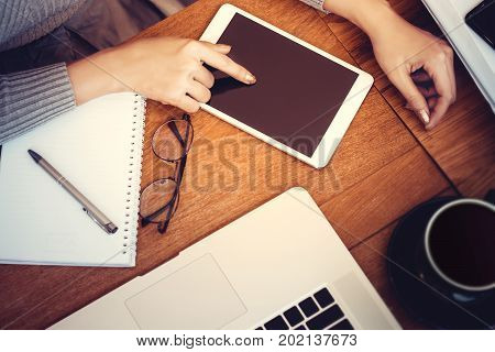 Technology concept: girl using a tablet with blank screen for copy space hardwood desktop and stationery on background