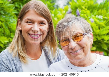 Portrait of elderly woman with damaged dental bridge smiling at the camera with her caretaker outdoor