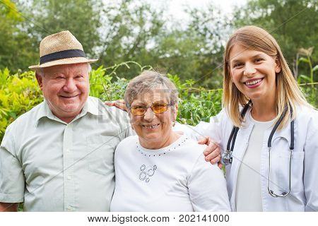 Friendly medical doctor with elderly couple smiling at the camera outdoor