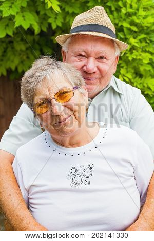Cute elderly couple in love hugging and smiling outdoor in the green garden