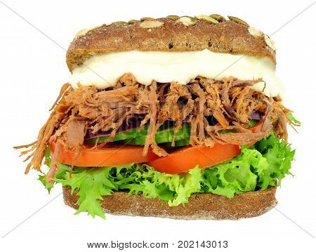 Shredded beef and salad filled pumpernickel bread sandwich isolated on a white background