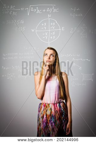 Thoughtful girl is solving equation. Young woman is doing something.