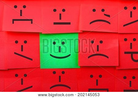 Emotions concept. Background of sticky notes. Green sticky note is among red sticky notes.
