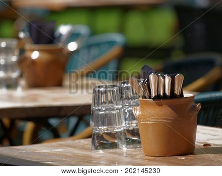 Glasses and silverware on tables of street restaurant