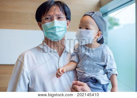 Portrait of Father holding Cute little Asian 18 months / 1 year old toddler baby boy child wearing protective medical mask Dad and son standing near the windows in clinic / hospital with copy space