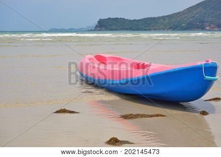 Colorful kayak on the beach. Pink and blue kayak.