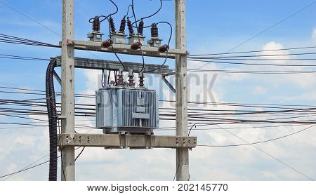 transformer and electricity post concept - Three phase transformer on high voltage electricity post with blue sky background and copy space for text
