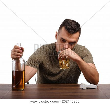 A depressed man in a green T-shirt is holding a big bottle and a transparent glass full of whiskey, isolated on a white background. A sad boozed guy with an alcoholic drink at a wooden table.