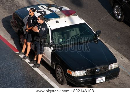 Los Angeles, California, USA - June 14, 2014: US police officer on duty at the police car