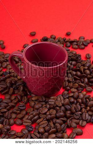 Empty coffee cup and coffee beans on a red background