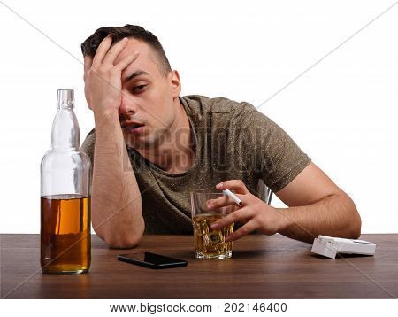 A boozed male is drinking a light brown liquor or whiskey from a glass at a desk, isolated on a white background. A big bottle full of alcohol beverage and a pack of cigarettes on a table. Copy space.