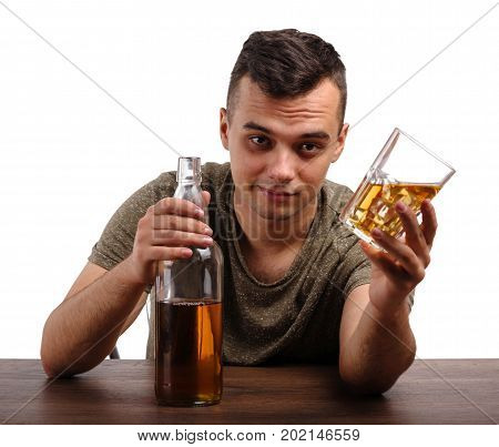 A male in a green T-shirt is showing a bottle and a glass full of whiskey or liquor, isolated on a white background. A boozed guy holding a full glass of alcoholic drink. Alcoholic addiction concept.