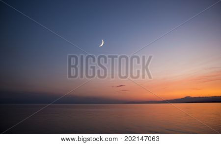 Colorful Sunset and moon in the sky, Issyk-Kul Lake. Kyrgyzstan.