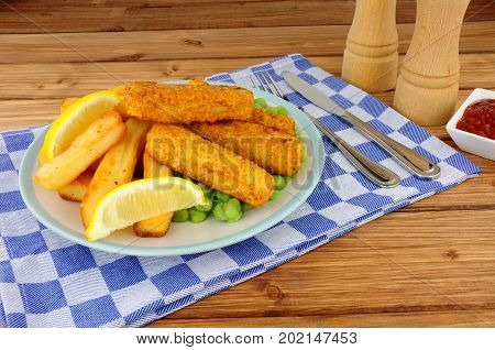 Batter covered fish fingers and chips meal with mushy peas on a wooden background