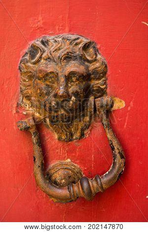 Lion Head Door Knockers On A Red Door