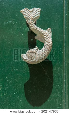Close-up View Of The Fish Shaped Knocker On A Green Wooden Door