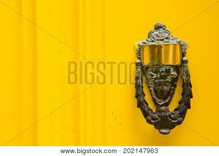 Decorative Bronze Door Handle On A Yellow Painted Door. Malta
