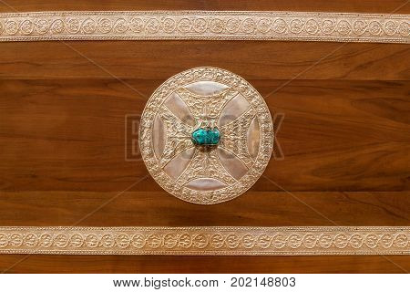wooden lid of  box with a cross and semiprecious stone