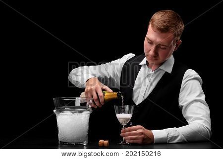 A confident, handsome bartender pouring alcohol champagne into a transparent glass on a saturated black background. A bowl with ice on a bar counter. A cute barman with a champagne bottle.
