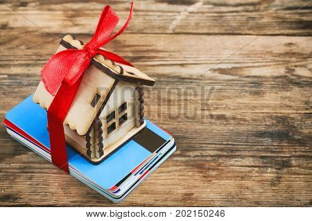 small house with ribbon on bunch of plastic credit debit cards on wooden table buying home concept