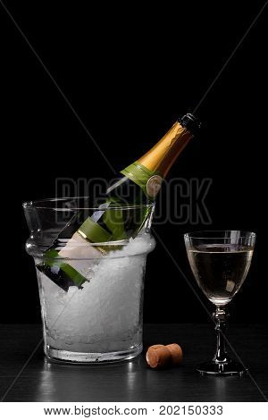 A close-up picture of a bottle of chilled champagne in a transparent bucket with crushed ice on a saturated black background. A wooden cork from a bottle and a glass of drink on a bar counter.