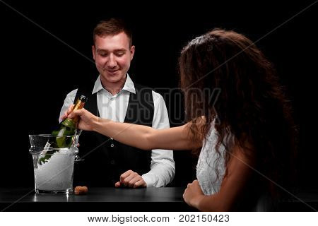 An attractive girl and a smiling barman flirting each other behind a bar counter on a saturated black background. A pretty girl takes a bottle of champagne from a transparent bucket.