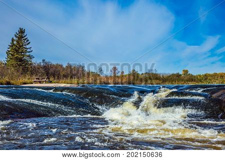 Foam water rapids on the smooth stones of the Winnipeg River. Old Pinawa Dam Provincial Heritage Park. The concept of travel