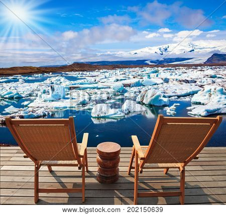 Two wooden deck chairs for admiring the sunset in Jokulsarlon. The concept of extreme northern tourism. Cool northern sun illuminates the Ice Lagoon, Iceland