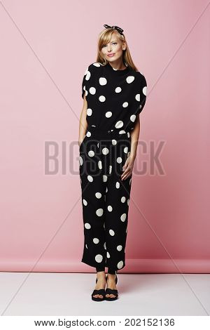 Portrait of posing babe in spotted jumpsuit smiling
