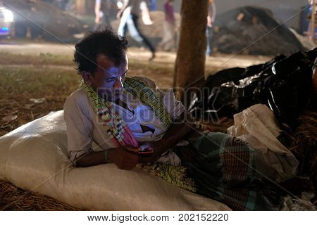 Dhaka, bangladesh, august 2017-a poor man using mobile phone sitting on ground for located at aftab nagar cow market in dhaka in bangladesh taken on 30, august 2017.