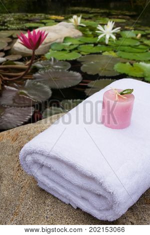 pink candle on white bath towel as spa set near lotus pond in the garden