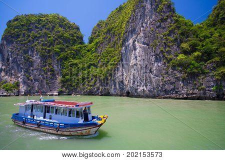 Popular famous tourist attraction in Vietnam. Tourist junk boat floating among limestone rocks at Halong Bay, Hanoi , South China Sea, landmark of Vietnam, Southeast Asia
