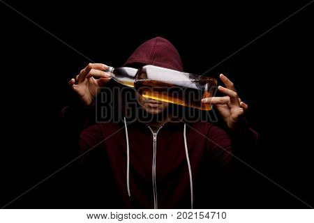 A handsome guy wearing a loose red hoodie with a big transparent bottle full of light alcoholic drink on a saturated black background. A desperate, lonely male with whiskey, beer or scotch in hands.