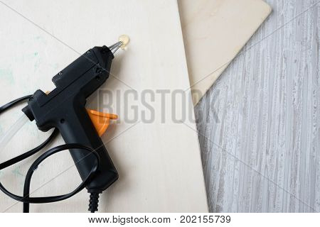 Electric hot glue gun on wood background. the concept of repair or creativity background