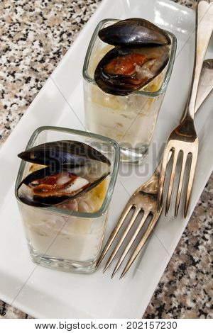 cooked mussel with soup in a shot glass