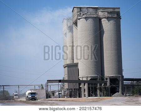 A huge cylindrical manufacturer factory on a blue sky background. Industrial factory building with modern engineering technologies. Air pollution, irrational production resources, ecology concept.