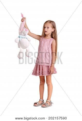 Full-length photo of a beautiful little girl with a big soft toy, isolated on a white background. A cute and shocked baby girl with long blonde hair is holding for ears a soft toy rabbit. Copy space.