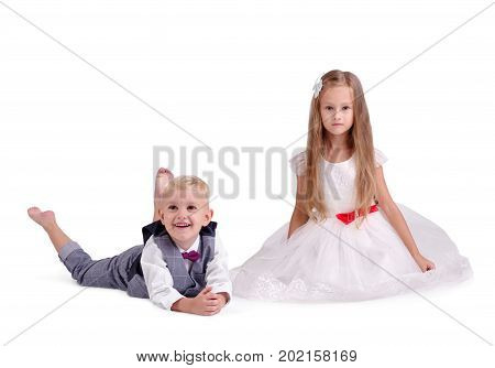 A photo of a pretty couple of little children wearing festive clothes, isolated on a white background. A smiling girl in a white dress with red bow and a little boy in a gray suit laying on a floor.