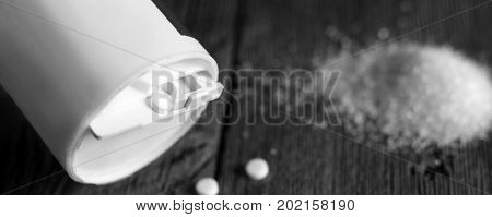 Sweetener Tablet And Sugar On Wooden Background